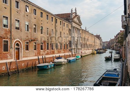 Channel With Boats And Historic Buildings On Embankment. Venice, Italy