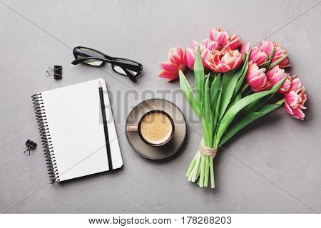Coffee clean notebook eyeglasses and beautiful tulip flower on stone table top view in flat lay style. Woman working desk with cozy breakfast.