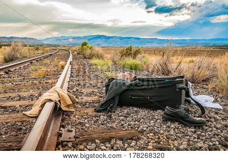An open suitcase by the railroad tracks