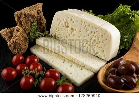 Slices of traditional sfella cheese of Peloponnese, Greece, on black tray with little tomatoes, rusk, lettuce, oregano and black olives