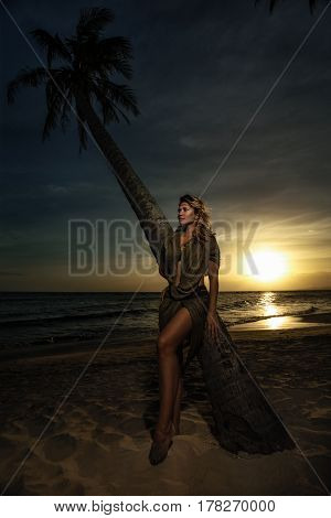 Portrait of woman with feathers in hair in tribal costume against sunset