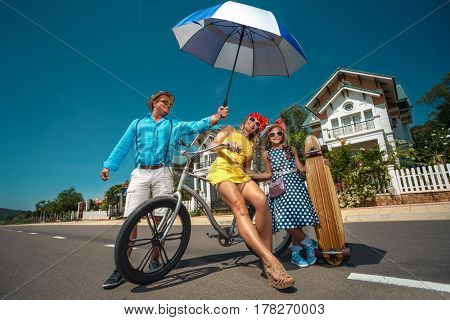 Vintage family walking on bike and  their daughter with skateboard in the suburb street