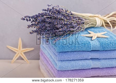 Stack of colorful bath towels with bouquet of lavender flowers and sea stars on light background. Pastel colors cotton towels. Hygiene fabricspa and textile concept