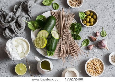 Ingredients for making green soba bowl - zucchini spinach soba yogurt on grey background top view. Healthy vegetarian food concept. Flat lay