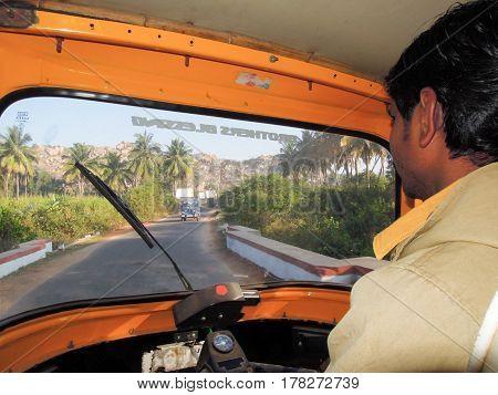 Hampi India - 11 January 2015: Driver of an auto rickshaw taxis on a road at Hampi on India