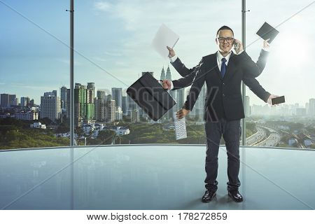 The businessman has a lot of hands to complete his work a powerful businessman concept.