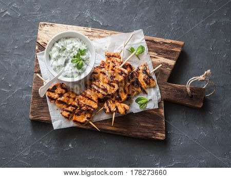 Grilled teriyaki chicken skewers and tzatziki sauce on a wooden board on a dark background top view. Delicious appetizers