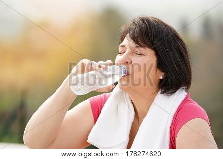 Overweight woman drinking water from bottle after exercising