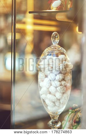 Rich variety of white chocolates candies in glass jars in display window of typical italian pastry in the street of Florence shop with light reflection on window