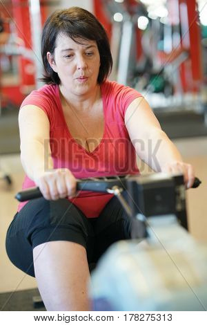 Overweight woman at the gym doing cardio exercises on rower