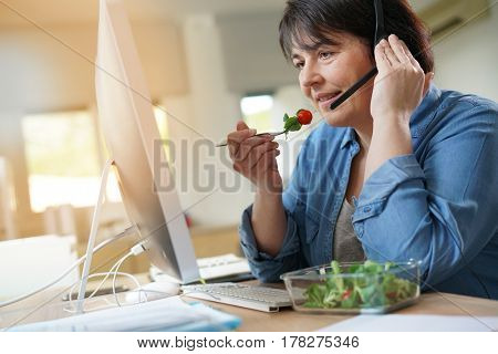 Telemarketing operator having lunch at work
