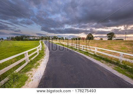 Curved Road With White Fences Leading To Village