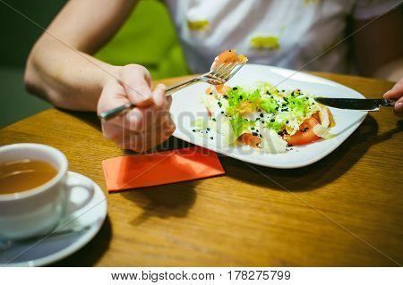 Young Blonde Woman Wearing White T-shirt With Print, Girl Eats Salad At Lunch Time, Sitting At A Tab