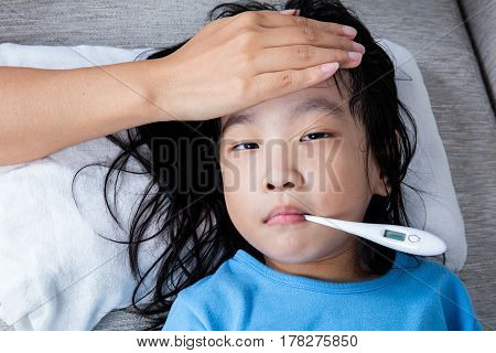 Asian Chinese Mother Measuring Little Girl Forehead For Fever