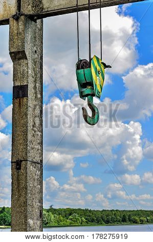 Yellow-green hook of a construction crane hanging on a rope on a background of clouds on a lake dam