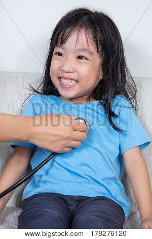 Smiling Asian Chinese Little Girl Examine By Doctor With Stethoscope