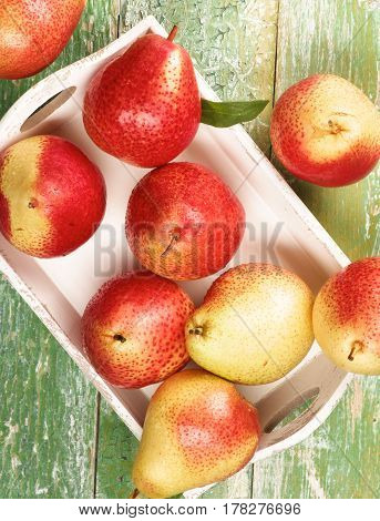 Arrangement of Ripe Yellow and Red Pears with Leafs in White Wooden Tray closeup on Green Wooden background. Top View