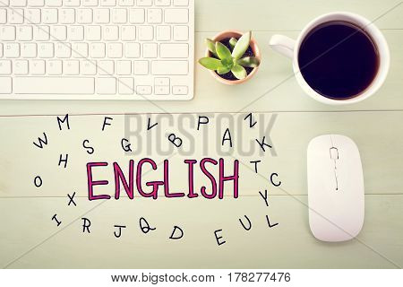 English concept with workstation on a light green wooden desk