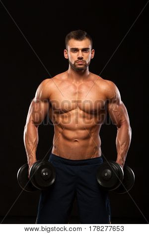 Muscular handsome man is training with dumbbells in gym. isolated on black background with copyspace.