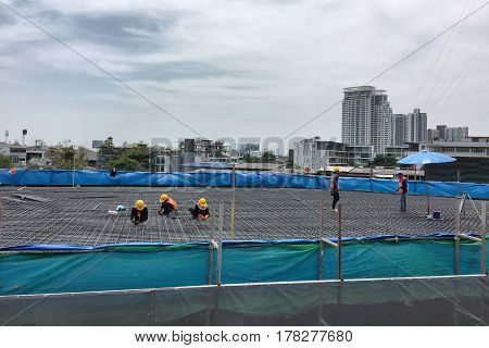 BANGKOK THAILAND 25 MARCH 2017: Workers fabricating column timber formwork and reinforcement bar at the construction site