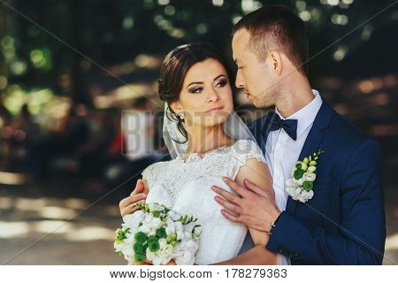 Groom Holds Bride's Shoulders Tender Standing With Her In The Park