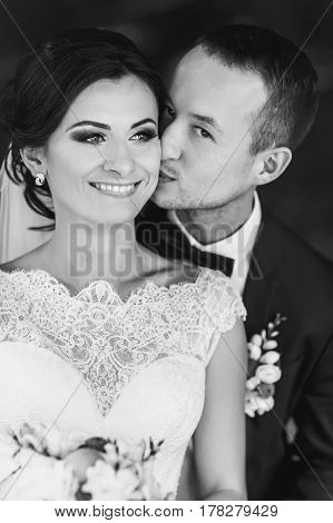 Groom Kisses Bride's Cheek Hugging Her From Behind
