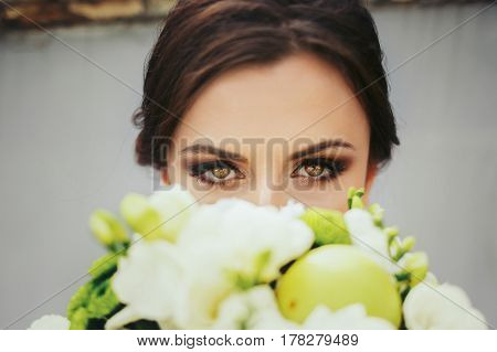Brunette bride with magic green eyes looks over a green wedding bouqet