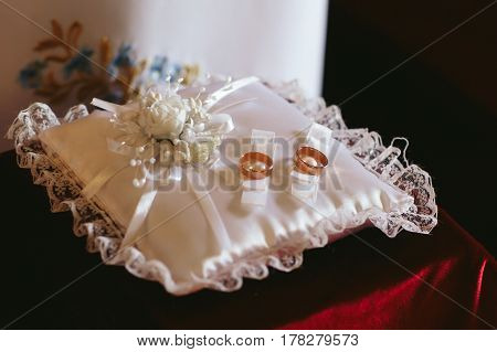 Golden wedding rings lie on the white silk pillow
