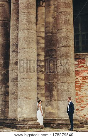 Groom Looks At Bride Which Stands Between The Pillars