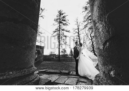 Groom Kisses A Bride While Wind Blows Her Veil Away