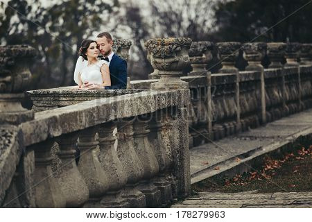 Groom Leans To A Bride Standing Behind A Half-ruined Balcony