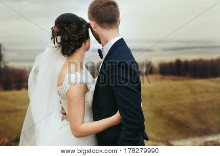 A Look From Behind On A Hugging Wedding Couple Looking At The Great Landscape In The Front Of Them