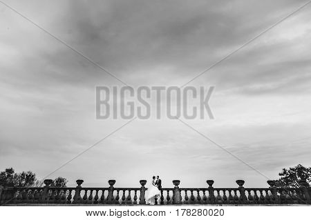 A Look From Afar On A Wedding Couple Sitting On The Balcony Under A Gray Sky
