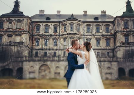 A Blurred Picture Of A Bride And Groom Kissing In The Front Of An Old Castle