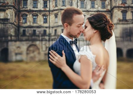 Groom Holds A Tender Bride In His Hands Standing On The Backyard Of An Old Castle