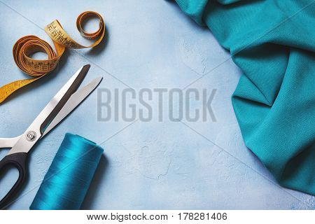 Background with tools for sewing: scissors threads cloth measuring tape. View from above