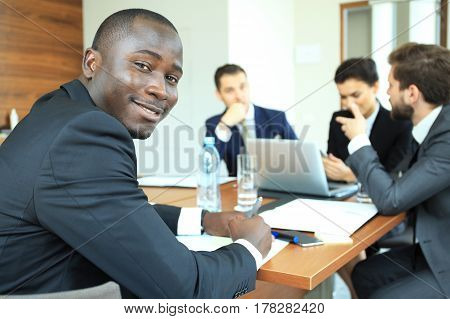 Smiling confident African businessman in a meeting with a group of multiracial co-workers seated at a conference table in the office