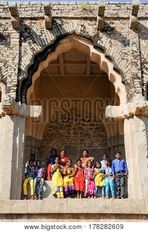 Hampi India - 12 January 2015: school class with teacher posing under the arch of Elephant Stables at Royal Centre on Hampi India