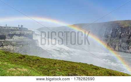 Vew of the great Gullfoss waterfalls and a spectacular rainbow in the canyon of Hvita river. Iceland