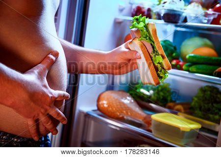 Hungry fat man holding a big sandwich in his hands and standing next to the open fridge. Unhealthy food.