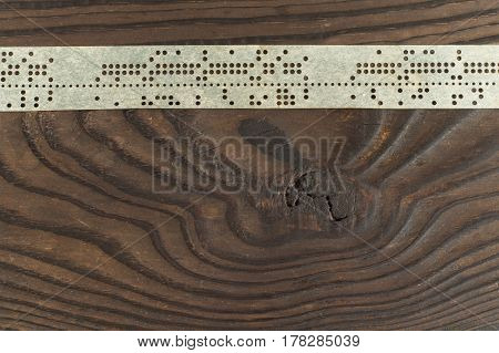 Strips of old punched tape on dark wooden surface