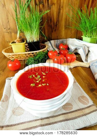 Vegetable soup consisting of beet ,tomatoes and other ingredients in a bowl, The soup is red on the wooden background