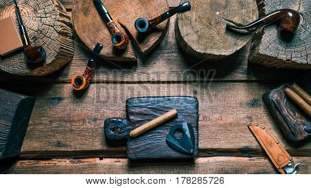 Cigar and cigar cutter on cutting board. Tobacco and pipes on wood desk. Close-up top view