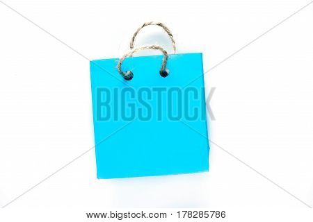 Tiny shopping bag of blue paper with rope handles. Isolated over white