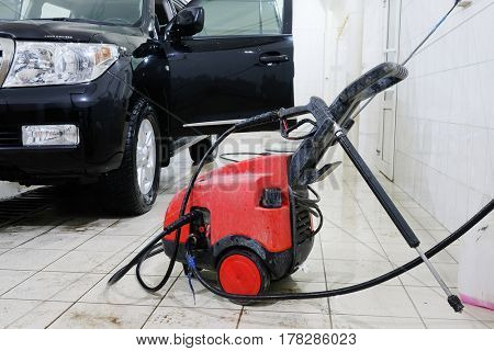 Kaluga, Russia - March, 21, 2017: high-pressure washing apparatus and a car in a car washing center