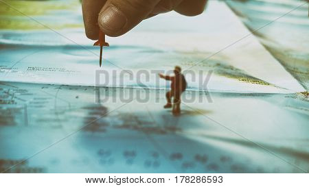 Hand Placing A Red Pin With Traveler Miniature Mini Figure With Backpack Walk On World Map. Travelli