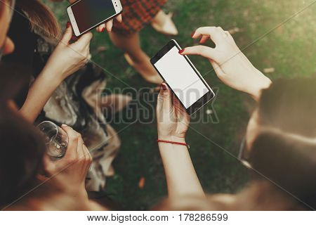 woman hands holding phone with empty screen and pointing. space for text. stylish elegant girls at party celebration sharing social media in sunny in park. staying online concept