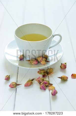 Rose flavoured tea in a white cup with dry rose buds scattered around. An exotic healthy middle eastern tea.