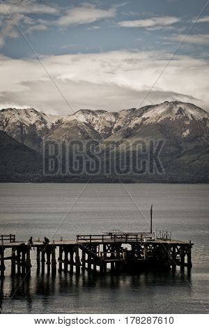 Two people on a dock, in a Patagonian Lake, with mountains sourrounding them