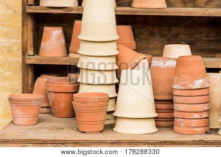 romantic idyllic plant table in the garden with old retro terracotta flower pot pots and garden tools. poster